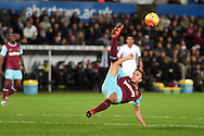 Mark Noble of West Ham gets airborne to clear the ball. Barclays Premier league match, Swansea city v West Ham Utd at the Liberty Stadium in Swansea, South Wales  on Sunday 20th December 2015.<br /> pic by  Andrew Orchard, Andrew Orchard sports photography.