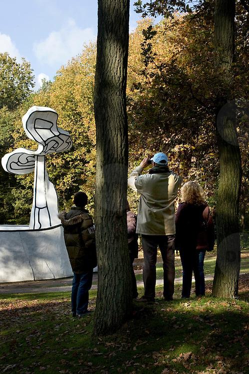Nederland Otterlo 29 oktober 2008 20081029 Foto: David Rozing ..Herft tafereel, man met familie maakt foto van Jardin d'email van Jean Dubuffet in de beeldentuin van het Kröller-Müller Museum. Op de voorgrond een boom in herfstkleuren, op de achtergrond een boom als kunststuk van de  Jardin d'email.Het museum ligt midden in het Nationale Park de Hoge Veluwe..Fall in The Netherlands, a man takes a picture in National Park de Hoge Veluwe, in the garden of the Kroller Muller museum. In the background is the object of art  Jardin d'email, by Jean Dubuffet..Foto: David Rozing