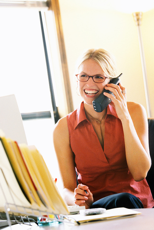 A young businesswoman in an office setting smiling and talking on the telephone.