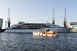 © Licensed to London News Pictures. 16/05/2015. London, UK. A Dunkirk Little Ship passes cruise ship Sunborn London as it parades in Royal Victoria Dock this evening. Over 20 Dunkirk Little Ships have gathered in London toay before leaving in the morning to continue their journey to Dunkirk to mark the 75th anniversary of the Dunkirk Evacuations. Photo credit : Vickie Flores/LNP