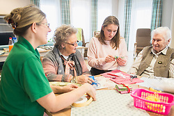 Senior women with girl and nurse doing craft activity at rest home