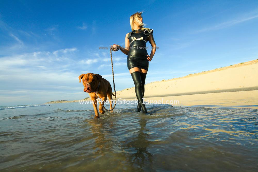 woman in latex dress walks her dog on the beach