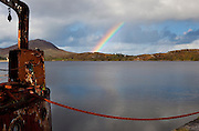 Mooring rop to wrecked ship, Ballinakill Bay, near Letterfrack, Ireland, with rainbow in the background, near Tully Mountain, Connemara, Galway, Ireland