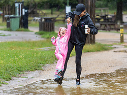 Licensed to London News Pictures. 07/08/202. London, UK. Summer washout. Mum Helen Burke-Smith with daughter Evelyn 4 get caught in torrential rain and large puddles in Richmond Park southwest London today as thunderstorms continue to hit the South East with further showers expected tomorrow. Yellow weather warnings for England have been issued for thunderstorms with heavy rain, and possible flooding as the bad weather is set to continue until Monday. However brighter weather is finally forecast for next week with highs of 23c. Photo credit: Alex Lentati/LNP