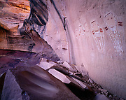 Sheltered alcove harboring pictographs of Five Faces and numerous sandstone boulders with bedrock mortars, Davis Canyon, Needles District, Canyonlands National Park, Utah.