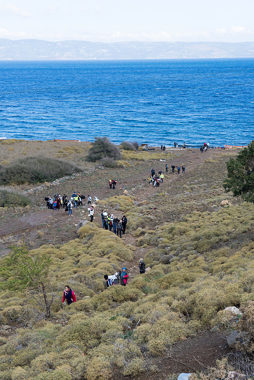 Having just landed on the beach in a small boat from Turkey, six miles (10 kilometers) away, migrants from Syria and Iraq walk up toward a road on the Greek island of Lesbos. They are among more than 500,000 migrants and refugees who have crossed from Turkey to the Greek islands in 2015.