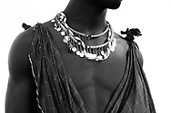 Maasai warrior dressed in traditional attire and adorned with jewelry.