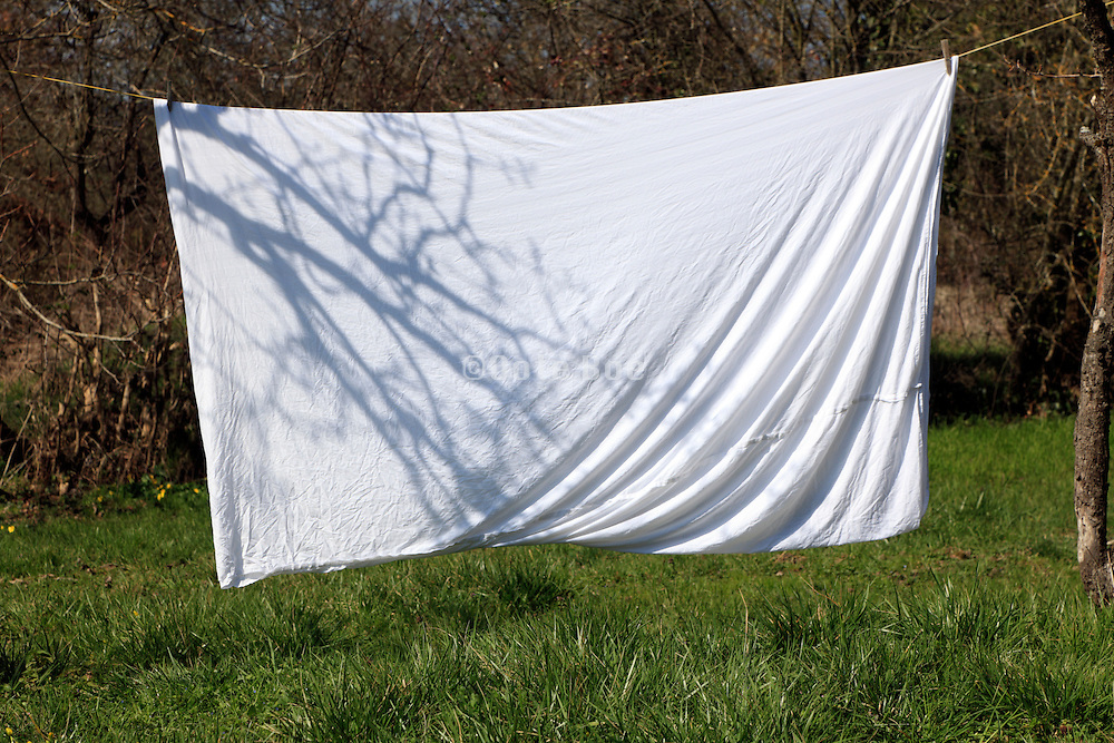 bed sheet drying outside on washing line