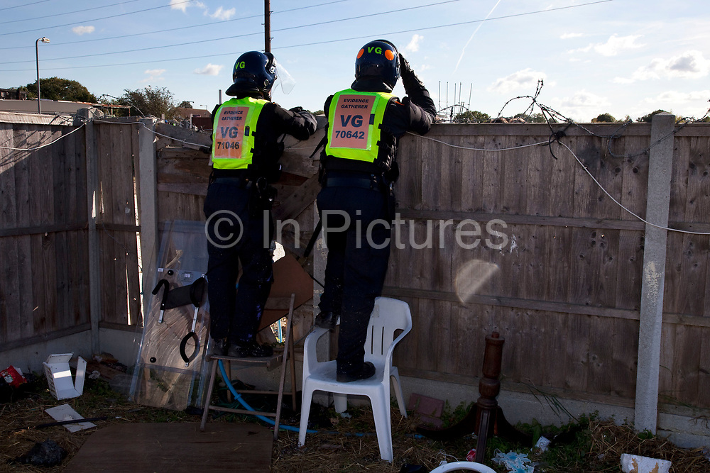 Police evidence gatherers look over a fence. Riot police and bailiffs were present on 20th October 2011, as the site was cleared of the last protesters chained to barricades. Dale Farm is part of a Romany Gypsy and Irish Traveller site in Crays Hill, Essex, UK<br /> <br /> Dale Farm housed over 1,000 people, the largest Traveller concentration in the UK. The whole of the site is owned by residents and is located within the Green Belt. It is in two parts: in one, residents constructed buildings with planning permission to do so; in the other, residents were refused planning permission due to the green belt policy, and built on the site anyway.