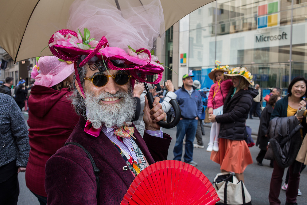 New York, NY, USA-27 March 2016. A man with a red fan, a colorful hat and a large white umbrella in the annual Easter Bonnet Parade and Festival.