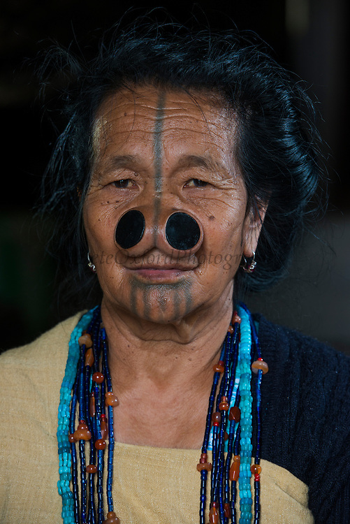 Apatani woman & facial tattoos & nose plugs or Yapin Hulo<br /> These plugs are made of a cane slice. This practice was to make them look unattractive to males from other tribes. These facial modifications are not longer used and has been outlawed<br /> Apatani Tribe<br /> Ziro Valley, Lower Subansiri District, Arunachal Pradesh<br /> North East India