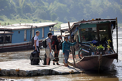 Tourists boarding river boats from a floating quayside installed by the MRC on the River.  Pak Beng, Oudomxay Province, Lao PDR