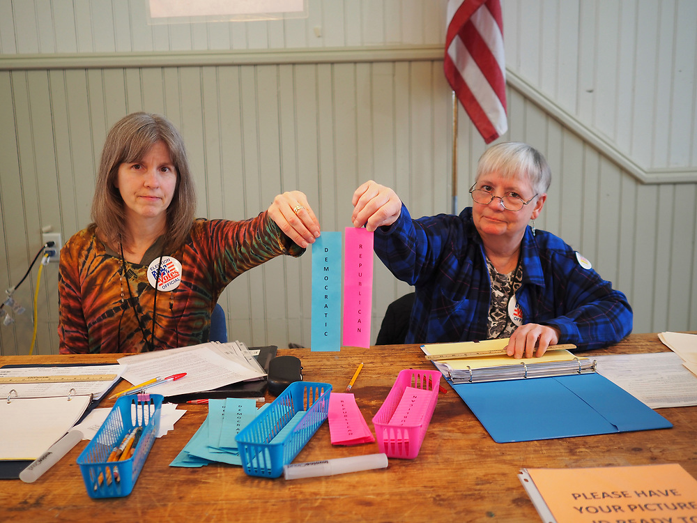 Sanbornton, New Hampshire poll workers display strips of paper indicating whether they will receive Democratic or Republican ballots after signing in to vote.