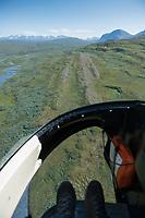 Feet in helicopter airtaxi flying over Padjelantaleden Trail towards Kvikkjokk, Lapland, Sweden