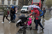 A family visiting the capital endure heavy rainfall on an autumn afternoon in Trafalgar Square, on 24th October 2019, in Westminster, London, England.