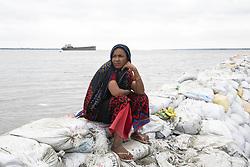 May 4, 2019 - Khulna, Bangladesh - Bangladeshi woman Rubi Begum (40) sits on sandbag embankment that was breached by high water in Khulna, Bani Shanta, as Cyclone Fani reached Bangladesh. Cyclone Fani, one of the biggest to hit India in years, barrelled into Bangladesh on May 4 after leaving a trail of deadly destruction in India. (Credit Image: © Ahmed Salahuddin/NurPhoto via ZUMA Press)