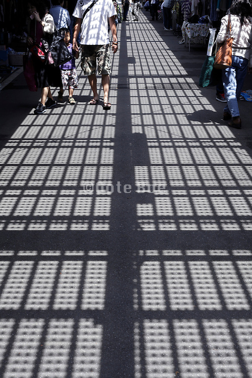shadow of overhead metal grating projected on people and road