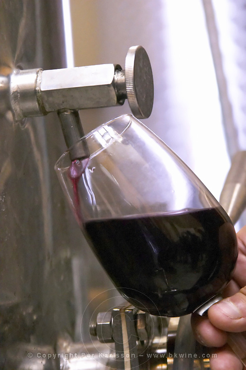 Domaine Haut-Lirou in St Jean de Cuculles. Pic St Loup. Languedoc. Pouring a wine sample in a glass. Stainless steel fermentation and storage tanks. Tank spout. France. Europe.