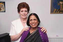 Elderly woman standing with carer smiling,