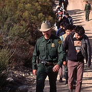 US Border Patrol leads a group of undocumented migrants off of Bob Maupin's property after Maupin and his citizen patrol had detained them. Please contact Todd Bigelow directly with your licensing requests.