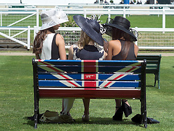 © Licensed to London News Pictures. 17/06/2014. Ascot, UK. Women sit on a bench featuring the Union Flag.  Day one at Royal Ascot 17th June 2014. Royal Ascot has established itself as a national institution and the centrepiece of the British social calendar as well as being a stage for the best racehorses in the world. Photo credit : Stephen Simpson/LNP