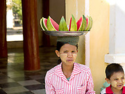 A woman, accompanied by a small boy, carries a metal tray on her head with sliced watermelon for sale at Shwedagon Pagoda, Yangon, the most revered Buddhist temple in Myanmar. The woman wears thanakha on her face, a traditional sunscreen/moisturiser.