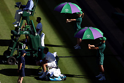 Umbrellas are used to shelter players from the sun on day One of the Wimbledon Championships at the All England Lawn Tennis and Croquet Club, Wimbledon.