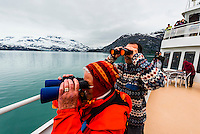 Passengers aboard the Wilderness Explorer (small cruise ship) looking for wildlife with binoculars, Glacier Bay National Park (a UNESCO World Heritage Site), Alaska USA.