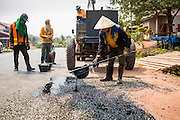 16 MARCH 2013 - HOUAYMOR, LAOS:  Workers on a road repair crew patch stretches of Highway 13 by putting down gravel and covering it with paving tar. PHOTO BY JACK KURTZ