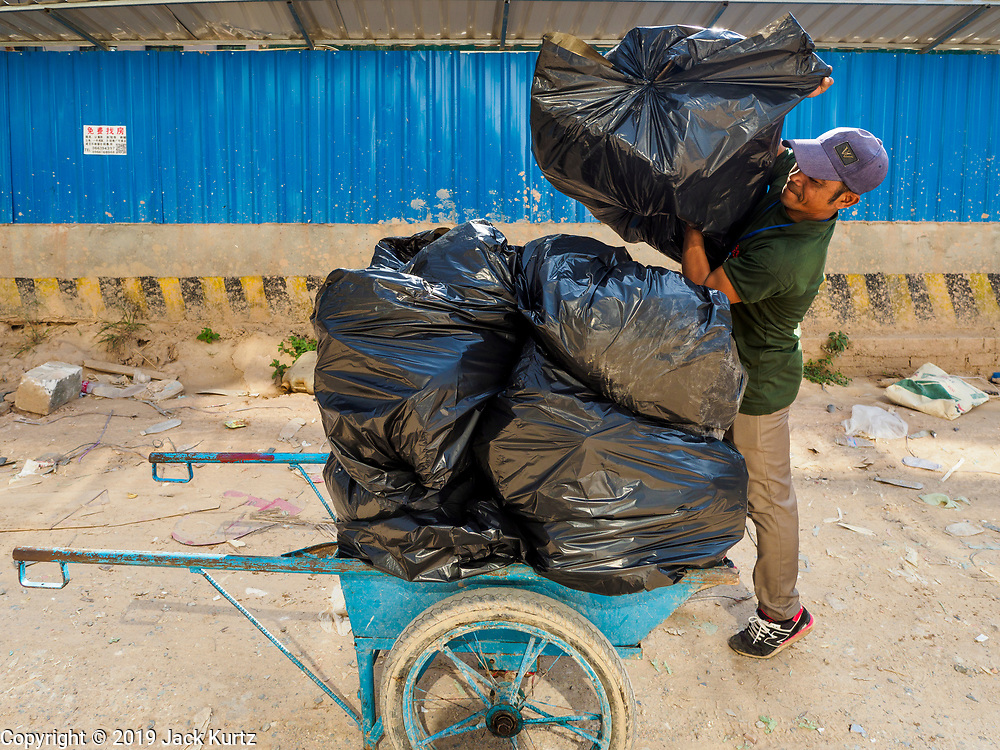 """15 FEBRUARY 2019 - SIHANOUKVILLE, CAMBODIA: A Cambodian laborer hauls garbage away from a casino in Sihanoukville. There are about 80 Chinese casinos and resort hotels open in Sihanoukville and dozens more under construction. The casinos are changing the city, once a sleepy port on Southeast Asia's """"backpacker trail"""" into a booming city. The change is coming with a cost though. Many Cambodian residents of Sihanoukville  have lost their homes to make way for the casinos and the jobs are going to Chinese workers, brought in to build casinos and work in the casinos.       PHOTO BY JACK KURTZ"""