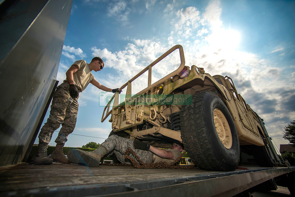 Airman 1st Class Dennis Fite, left, and Airman 1st Class Brinkley Owens, both 100th Logistics Readiness Squadron ground transportation operators, conduct vehicle tie down procedures on RAF Mildenhall, England, July 20, 2018. Ground transportation Airmen deliver heavy equipment to units on and off base, and they also provide transportation to official appointments and ensure Airmen receive their mail by doing daily mail runs to and from RAF Alconbury. (U.S. Air Force photo by Senior Airman Christine Groening)