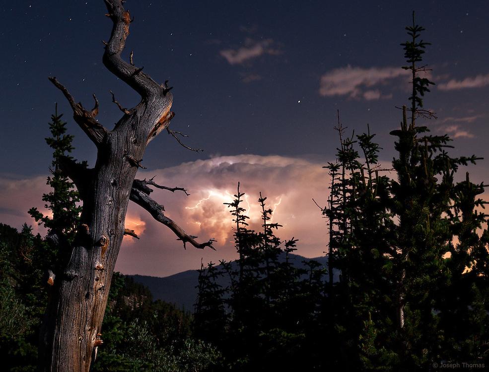 Lightning illuminates a distant thunderstorm while the moon illuminates the landscape.
