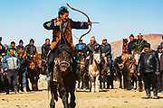 Kazakh eagle hunters competing on horseback with bow and arrow at an eagle festival , Altai Mountains, Bayan Ulgii, Mongolia
