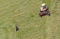 THEMENBILD - Landwirte mit Traktor mit Maehwerk und Rechen bei der Heuernte auf einem steilen Hang, aufgenommen am 11. August 2015, Maishofen, Österreich// farmers with tractor and rakes mowing hay in a Field, Maishofen, Austria on 2015/08/11. EXPA Pictures © 2015, PhotoCredit: EXPA/ JFK