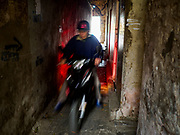"22 DECEMBER 2017 - HANOI, VIETNAM: A man drives motorbike through a passageway in the old quarter of Hanoi. The old quarter is the heart of Hanoi, with narrow streets and lots of small shops but it's being ""gentrified"" because of tourism and some of the shops are being turned into hotels and cafes for tourists and wealthy Vietnamese.    PHOTO BY JACK KURTZ"