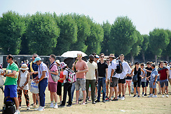 © Licensed to London News Pictures. 06/07/2018. LONDON, UK. Spectators queue for day tickets in Wimbledon Park to the Wimbledon Tennis Championships.  Temperatures forecast to approach 30C mean that the majority have taken precautions to protect themselves from the sun by wearing sunglasses and sunhats.  Photo credit: Stephen Chung/LNP