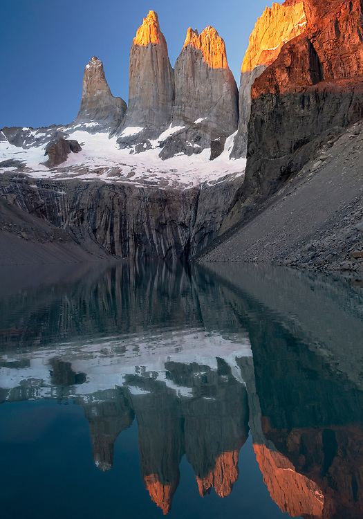 The sun hits the tips of the majestic peaks of Torres del Paine, reflected on a blue lake at sunrise, Chile, South America.