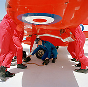 Officer pilots of the elite 'Red Arrows', Britain's prestigious Royal Air Force aerobatic team, lean against a wing of their Hawk jet in a pre-flight briefing while a member of their ground crew positions some wheel chocks. The highly-skilled engineer is known as a 'Blue' but the 'Reds' discuss  flight plans. Eleven trades skills are imported from some sixty that the RAF employs and teaches. It is mid-day and only their flying boots and red legs are seen with the RAF roundel emblem is on the underside of the wing. The better-educated officers in the armed forces enjoy a more privileged lifestyle than their support staff. In the aerobatic squadron, the Blues outnumber the pilots 8:1. Without them, the Red Arrows couldn't fly. Some of the team's Hawks are 25 years old and their air frames require constant attention, with increasingly frequent major overhauls due.