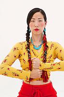 Asian woman in Tibetan braids with her hands in power fits hands mudra.