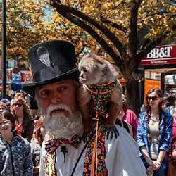 York, PA / USA - May 8, 2016 A bearded man with a tall hat and a monkey on his shoulder entertained people at the City of York Annual Mother's Day Street Fair.: