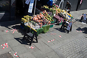 At the beginning of the fourth week of the UK government's lockdown during the Coronavirus pandemic, and with 120,067 UK reported cases with 16,060 deaths, a market stalll selling fruit on the Walworth Road also has social distancing marks on the pavement, in South London, on 20th April 2020, in London, England.