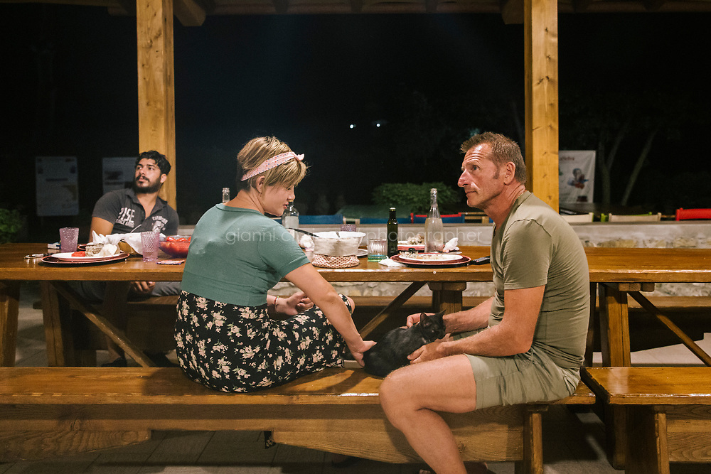 """TALAMONE, ITALY - 26 AUGUST 2019: (R-L) Fisherman and activist Paolo Fanciulli is seen here with his wife Sandra Galvis, a fellow Greenpeace activist from Colombia, and his assistant after dinner in the garden he converted into a restaurant, in Talamone, Italy, on August 26th 2019.<br /> <br /> In 2006, fisherman Paolo Fanciulli used government funds and the donations from his loyal excursion clients to fund a project in which they protected the local waters from trawling by dropping hundreds of concrete blocks around the seabed. But his true dream was to lay down works of art down on the sea floor off the coast of Tuscany. His underwater art dreams came true when the owner of a Carrara quarry, inspired by Mr. Fanciulli's vision, donated a hundred marble blocks to the project.<br /> Mr. Fanciulli invited sculptors to work the marble and set up kickstarter accounts, boat tours and dinners to fund the project. The acclaimed British artist Emily Young carved a ten-ton """"Weeping Guardian"""" face, which was lowered with other sculptures into the water in 2015.<br /> Since then, coral and plant life have covered the sculptures and helped bring back the fish. And Paolo the Fisherman is catching as many of them as he can."""