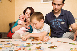 Polish mother comforting baby daughter whilst father is playing with son,