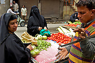 Two women covered with burka in the old street of the bazaar area in Srinagar. Women often raise the veil to choose the items they buy.