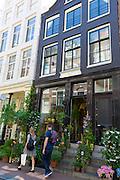 Shoppers pass traditional florist shop in the Nine Streets - De Negen Straatjes - 9 Streets district of Jordaan, Amsterdam