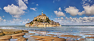 """Scenic view of the tidal island  of Mont Saint Michel at high tide surrounded and its medieval abbey of Saint Michel. Normandy France.<br /> <br /> The tides vary greatly, at roughly 14 metres (46 ft) between highest and lowest water marks. Popularly nicknamed """"St. Michael in peril of the sea"""" by medieval pilgrims making their way across the flats, the mount can still pose dangers for visitors who avoid the causeway and attempt the hazardous walk across the sands from the neighbouring coast. .<br /> <br /> Visit our MEDIEVAL PHOTO COLLECTIONS for more   photos  to download or buy as prints https://funkystock.photoshelter.com/gallery-collection/Medieval-Middle-Ages-Historic-Places-Arcaeological-Sites-Pictures-Images-of/C0000B5ZA54_WD0s"""