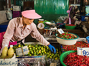 27 SEPTEMBER 2016 - BANGKOK, THAILAND: A vendor sets up her booth selling limes and chilies in the market in the Samut Songkhram train station. The train from Baen Laem to Samut Songkhram (Mae Khlong) recently resumed service. The 33 kilometer track was closed for repair for almost a year. In Samut Songkhram, the train passes over the market. Vendors pull their stands out of the way and people step out of the way as the train passes through the market. It is one of the most famous train stations in Thailand and has become an important tourist attraction in the community.     PHOTO BY JACK KURTZ