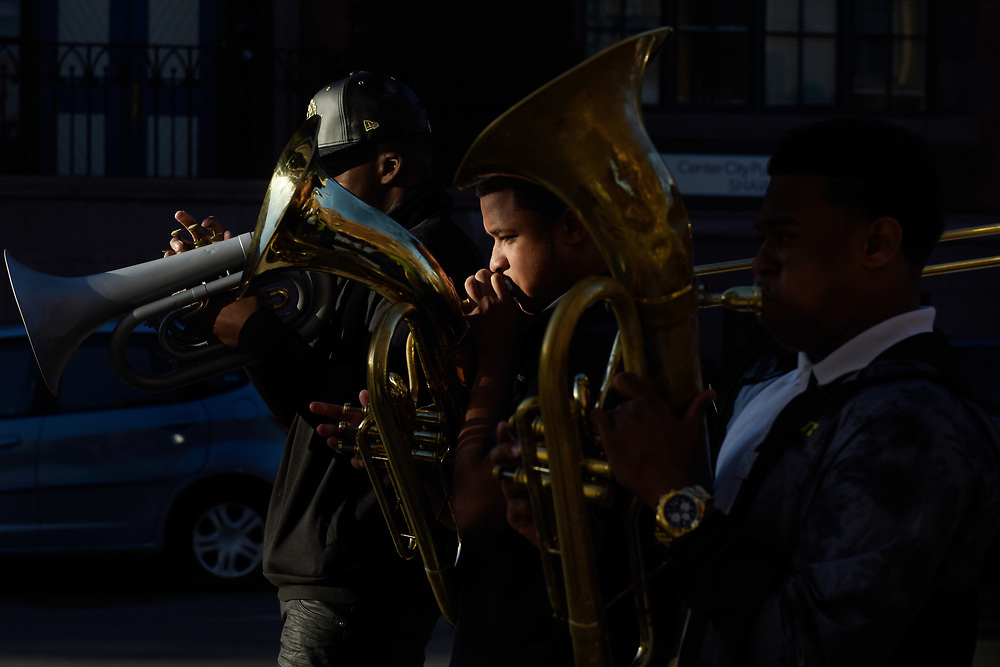 The United House of Prayer marching band parades down N street in the Shaw neighborhood in evening light.