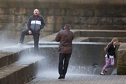 """© Licensed to London News Pictures. 09/11/2015. Bridlington, UK. FRAME 8 OF 9. A man poses for a photograph on the sea defences at the sea side town of Bridlington & gets caught out by a huge wave. The Yorkshire region was hit by severe gales this afternoon with winds up to 60mph. The Met Office warned West Yorkshire to expect gales and locally severe gales over high ground, with some """"very gusty"""" winds to the east of high ground as well.<br /> Photo credit: Andrew McCaren/LNP"""