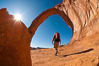 A young man hikes below Corona Arch near Moab, Utah.